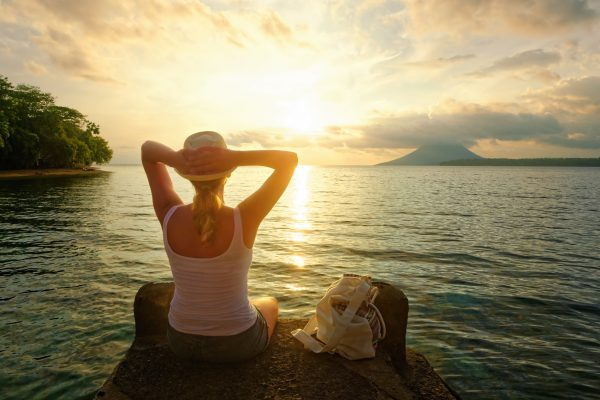 Rear view of a romantic young woman sitting on the pier enjoying stunning sunset